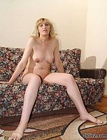 A naked blond brunette poses on the couch naked