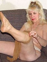 A mature long-haired blond in pantyhose is undressing