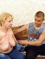 A busty mature blond is giving head