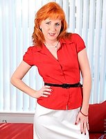 Naughty milf Sasha Brand strips off her clothes and fondles her red haired Anilos pussy on the sofa